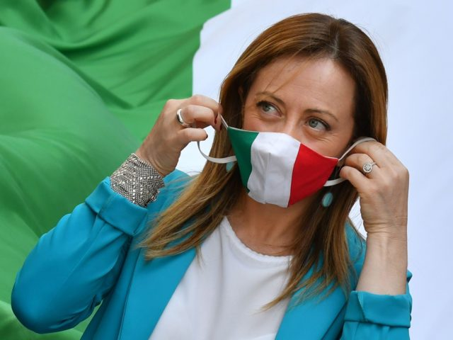 Head of the Brothers of Italy (FdI) party, Giorgia Meloni adjusts her face nask in the colors of the Italian flag, as she marches during a united rally along with the League party and the Forza Italia (FI) party for a protest against the government on June 2, 2020 on …