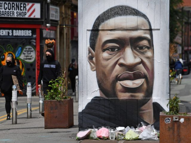 Flowers are seen beneath a mural of George Floyd, by street artist Akse, ahead of a demonstration in Manchester, northern England, on June 6, 2020, to show solidarity with the Black Lives Matter movement in the wake of the killing of George Floyd, an unarmed black man who died after …