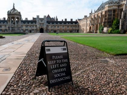 A sign advising people to social distance is displayed on the Great Court at Trinity College, part of the University of Cambridge, in Cambridge, east England on October 14, 2020. - Going to Cambridge had always been a dream for Matthew Omoefe Offeh, one of a growing number of black …