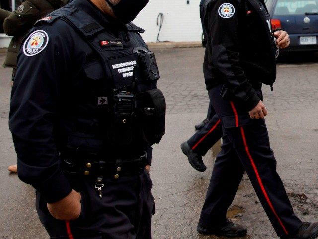 Police gather in the parking lot of Adamson Barbecue, an Etobicoke business that has defied provincial shutdown orders, on November 25, 2020 in Toronto, Canada. - Amid a spike in hospitalizations due to Covid-19, the province of Ontario issued a shutdown of all indoor and outdoor dining of restaurants, gyms, …