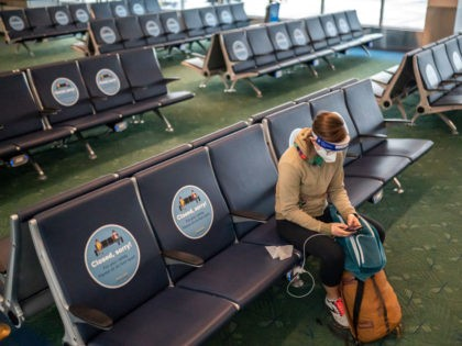 PORTLAND, OR - NOVEMBER 25: A traveler checks their phone while waiting for a flight at Portland International Airport on November 25, 2020 in Portland, Oregon. Millions of Americans traveled by plane ahead of the Thanksgiving holiday, despite the CDC recommending families stay home. (Photo by Nathan Howard/Getty Images)