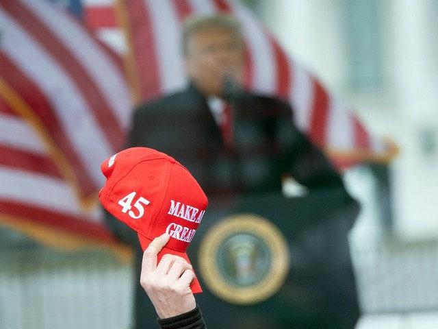 "A person raises a ""Make America Great"" hat as US President Donald Trump speaks to supporters from The Ellipse near the White House on January 6, 2021, in Washington, DC. - Thousands of Trump supporters, fueled by his spurious claims of voter fraud, are flooding the nation's capital protesting the …"