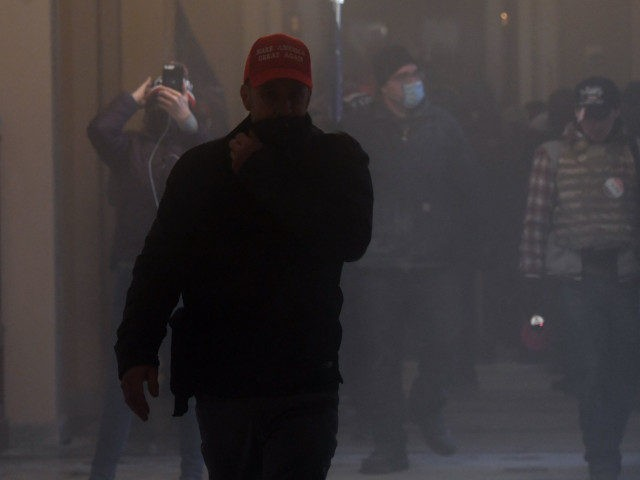 Supporters of US President Donald Trump enter the US Capitol as tear gas fills the corridor on January 6, 2021, in Washington, DC. - Demonstrators breeched security and entered the Capitol as Congress debated the a 2020 presidential election Electoral Vote Certification. (Photo by Saul LOEB / AFP) (Photo by …