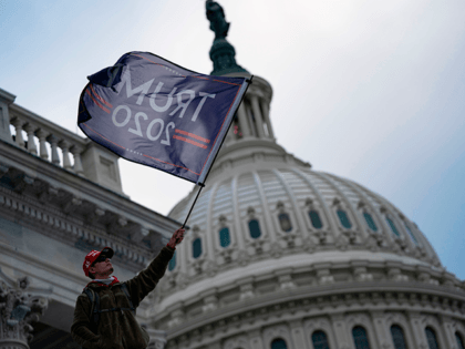 A person waves a Trump 2020 flag as supporters of US President Donald Trump protest outside the US Capitol on January 6, 2021, in Washington, DC. - Demonstrators breeched security and entered the Capitol as Congress debated the a 2020 presidential election Electoral Vote Certification. (Photo by ALEX EDELMAN / …