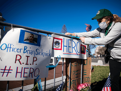 Anne Seymour, a crime victim advocate, creates a makeshift memorial for U.S. Capitol Police Officer Brian Sicknick, who was fatally injured when a pro-Trump mob stormed and entered the Capitol Building on Wednesday, near the West Front of the U.S. Capitol on January 9, 2021 in Washington, DC. A pro-Trump …