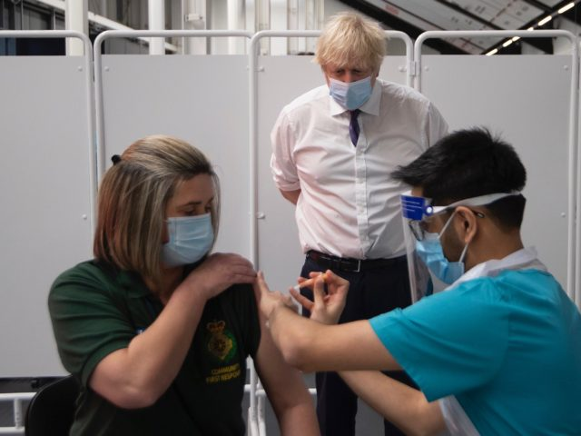 Britain's Prime Minister Boris Johnson watches as an individual is injected with a Covid-29 vaccine at a mass vaccination centre at Ashton Gate stadium in Bristol, southwest England on January 11, 2021. - Seven mass coronavirus vaccination sites opened across England on Monday as the government races to dose millions …