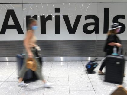 Passengers wearing face masks as a precautionary measure against COVID-19, walk through the arrivals hall after landing at London Heathrow Airport in west London, on January 15, 2021. - International travellers will need to present proof of a negative coronavirus test result in order to be allowed into England, or …