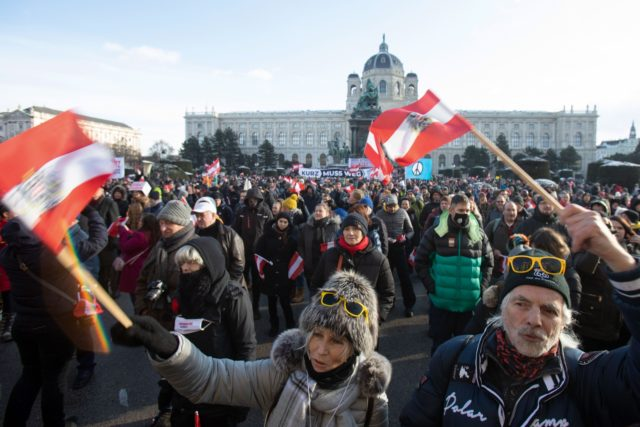 Demonstrators wave the Austrian flag during a protest against the novel coronavirus (Covid-19) restrictions and hold a banner 'Kurz must go' at the Maria Theresien Platz in Vienna, Austria on January 16, 2021. (Photo by ALEX HALADA / AFP) (Photo by ALEX HALADA/AFP via Getty Images)