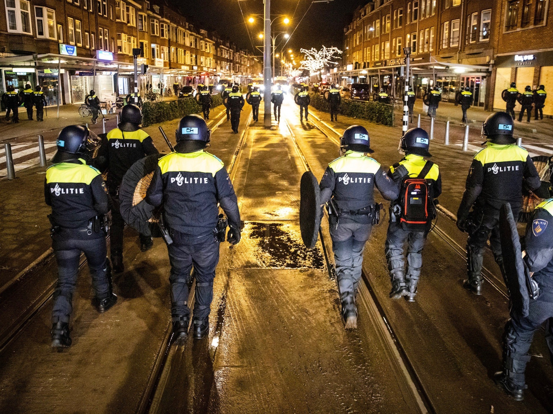 TOPSHOT - Dutch police officers patrol in the streets of Rotterdam, during the curfew time, on January 26, 2021, a day after police clashed with groups of demonstrators protesting against the introduction of new measures, including the curfew, to fight against the spread of the Covid-19. - In South Rotterdam and in the city center, several people were arrested for, among other things, gathering and not being able to show proof of identity. The police are massively present in the city after the riots of the day before and check people walking in groups on the street. (Photo by STR / ANP / AFP) / Netherlands OUT (Photo by STR/ANP/AFP via Getty Images)