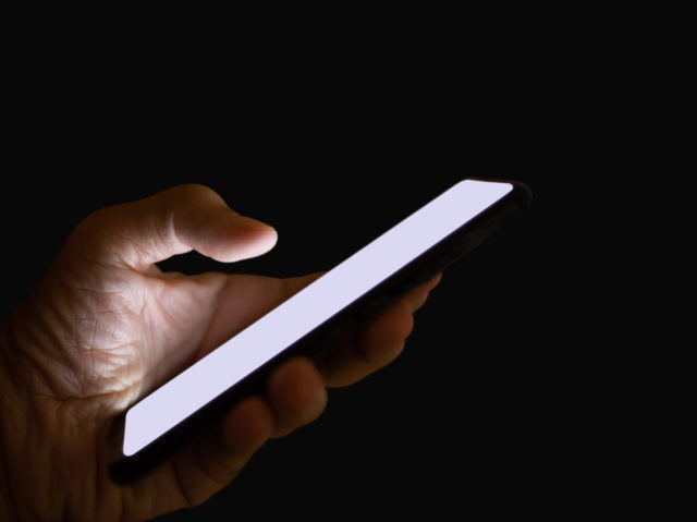Close-up of hand holding mobile phone on dark background. Concept hacker using mobile phone to steal information online