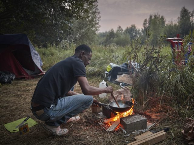 CALAIS, FRANCE - AUGUST 15: A refugee cooks on a small fire in a makeshift camp in wasteland on the outskirts of Calais after recent evictions by police at previously established camps have forced refugees to more remote areas on August 15, 2020 in Calais, France. A spate of good …