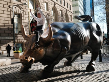 NEW YORK, NEW YORK - NOVEMBER 24: A man sits on the Wall street bull near the New York Stock Exchange (NYSE) on November 24, 2020 in New York City. As investor's fear of an election crisis eases, the DowJones Industrial Average passed the 30,000 milestone for the first time …