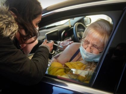 MANCHESTER, ENGLAND - DECEMBER 17: Joan Burgess receives the Pfizer/BioNTech vaccine at a drive-thru COVID-19 vaccination centre in Hyde on December 17, 2020 in Manchester, England. The coronavirus drive-through vaccine centre is believed to be the first in the world. (Photo by Christopher Furlong/Getty Images)