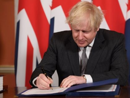 LONDON, ENGLAND - DECEMBER 30: Prime Minister, Boris Johnson signs a page of the Brexit trade deal with the EU in number 10 Downing Street on December 30, 2020 in London, United Kingdom. The United Kingdom and the European Union agreed a Trade and Cooperation Agreement, an Agreement on Nuclear …