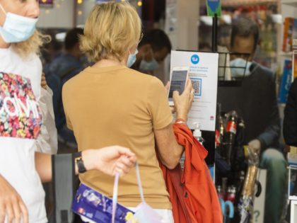 SYDNEY, AUSTRALIA - JANUARY 03: A shopper uses a QR code at the entrance of a store along The Corso in Manly on January 03, 2021 in Sydney, Australia. Face masks are now compulsory in certain indoor settings across NSW as the state continues to record new COVID-19 cases in …