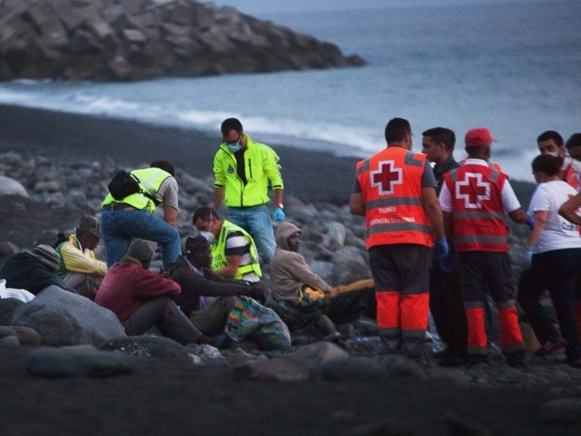 Members of the Red Cross tend to would-be immigrants upon their arrival in Tazacorte, on the Spanish Canary Island of La Palma, on June 30, 2014. The 12 sub-Saharan migrants, who reached the beach of Los Tarajales in a canoe, have been transferred to the police station of Santa Cruz …