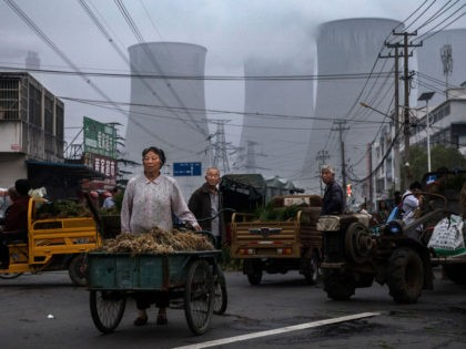 HUAINAN, CHINA - JUNE 13: Chinese street vendors sell vegetables at a local market outside a state owned Coal fired power plant near the site of a large floating solar farm project under construction by the Sungrow Power Supply Company on a lake caused by a collapsed and flooded coal …