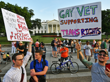 """Protesters gather in front of the White House July 26, 2017, in Washington, DC. Trump announced on July 26 that transgender people may not serve """"in any capacity"""" in the US military, citing the """"tremendous medical costs and disruption"""" their presence would cause. / AFP PHOTO / PAUL J. RICHARDS …"""