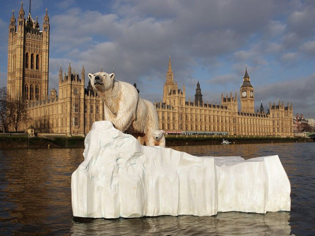 LONDON, ENGLAND - JANUARY 26: A 16 foot high sculpture of a polar bear and cub, afloat on a small iceberg, passes in front of the Houses of Parliament on the River Thames on January 26, 2009 in London, England. The sculpture was launched to provide a warning to members …