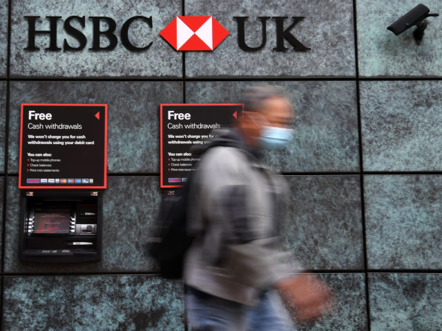 A pedestrian wearing a face mask or covering due to the COVID-19 pandemic, walks past a branch of a HSBC bank in central London on August 3, 2020. - HSBC on Monday revealed a 69-percent slump in net profits, joining a number of major bank whose earnings have been slammed …