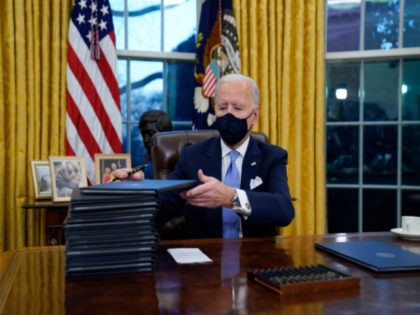 In this Jan. 20, 2021, file photo, President Joe Biden signs his first executive orders in the Oval Office of the White House in Washington. Six of Biden's 17 first-day executive orders dealt with immigration, such as halting work on a border wall in Mexico and lifting a travel ban …
