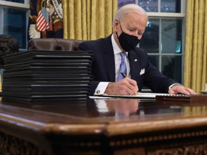 WASHINGTON, DC - JANUARY 20: U.S. President Joe Biden prepares to sign a series of executive orders at the Resolute Desk in the Oval Office just hours after his inauguration on January 20, 2021 in Washington, DC. Biden became the 46th president of the United States earlier today during the …