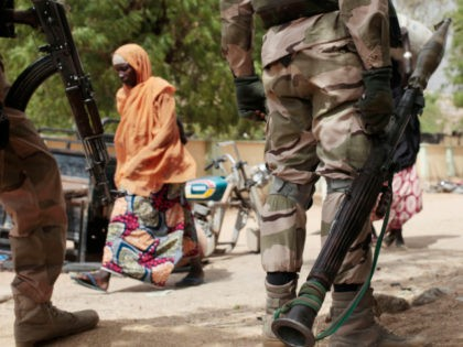 In this photo taken Wednesday, April 8, 2015, a woman walks past Nigerian Soldiers at a checkpoint in Gwoza, Nigeria, a town newly liberated from Boko Haram. Each day brings new reports of atrocities, with mass graves being discovered in towns seized back from the militants who had set up …