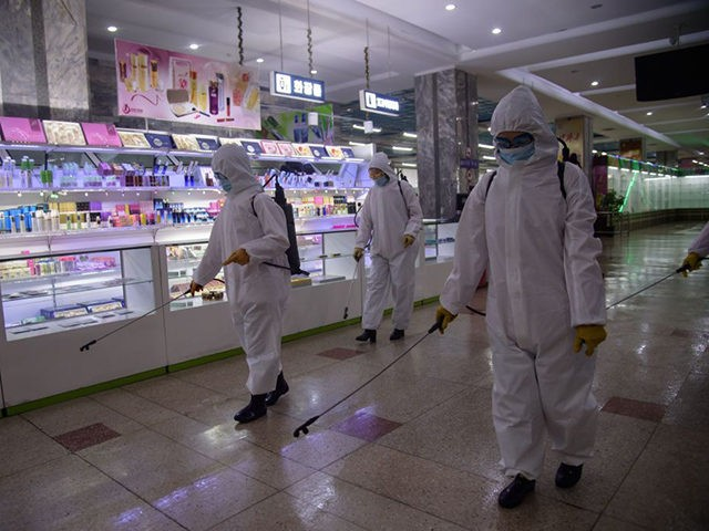 Health workers spray disinfectant inside the Pyongyang Department Store No. 1 prior to opening for business, in Pyongyang on December 28, 2020. (Photo by KIM Won Jin / AFP) (Photo by KIM WON JIN/AFP via Getty Images)