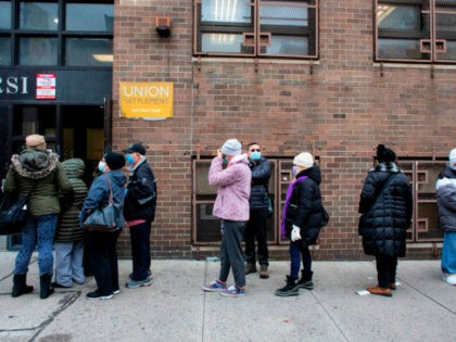 People wait in line for Pfizer Covid-19 vaccines at the opening of a new vaccination site at Corsi Houses in Harlem New York on January 15, 2021. - Pfizer expects lower coronavirus vaccine deliveries for a stretch beginning in late January in order to lift output later this winter and …