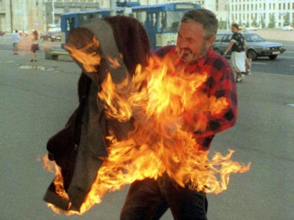 A man who identified himself as Nikolai Vasilenko pulls off his burning coat in the central square in Minsk, Belarus Wednesday, July 2, 1997. Vasilenko, 42, tried to burn himself during a protest against the authoritarian rule of Belarusian President Alexander Lukashenko, but as soon as the flames blazed up, …