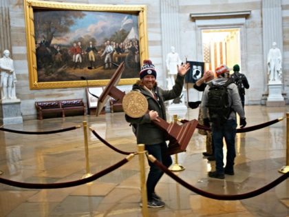 WASHINGTON, DC - JANUARY 06: A pro-Trump protester carries the lectern of U.S. Speaker of the House Nancy Pelosi through the Roturnda of the U.S. Capitol Building after a pro-Trump mob stormed the building on January 06, 2021 in Washington, DC. Congress held a joint session today to ratify President-elect …