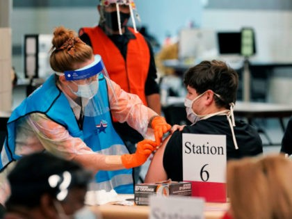 A health care worker administers a COVID-19 vaccination at the new Alamodome COVID-19 vaccine site, Monday, Jan. 11, 2021, in San Antonio, Texas. Officials say the site is providing 1,500 vaccinations per day. (AP Photo/Eric Gay)