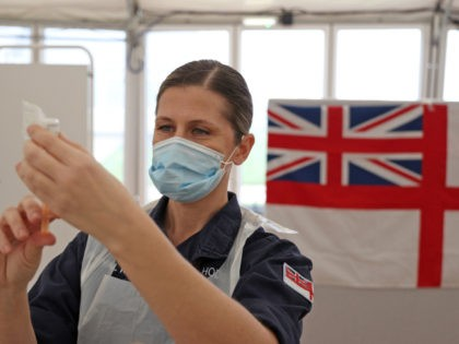 Royal Navy medics prepare syringes ahead of giving injections of the Oxford/AstraZeneca Covid-19 vaccine to members of the public at a vaccination centre set up at Bath racecourse in Bath, southwest England on January 27, 2021. - Over 30 new coronavirus vaccination centres were set to open around England this …