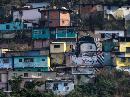 A mural depicting Venezuelan late leader Hugo Chavez is seen at Guarataro slum in Caracas, on May 24, 2020 during the COVID-19 coronavirus pandemic. - Overcrowded neighbourhoods and a big population within poverty levels are a big challenge Latin American countries are facing during this global pandemic. (Photo by Federico …