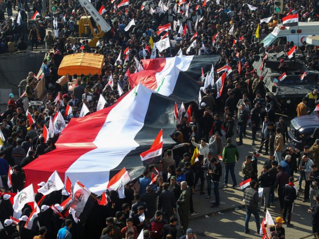 "Iraqi demonstrators lift a giant national flag during a rally marking the first anniversary of the killing of Iraqi commander Abu Mahdi al-Muhandis (L) and Iranian Revolutionary Guards commander Qasem Soleimani, in Tahrir square in the capital Baghdad on January 3, 2021. - Thousands of Iraqi mourners chanted ""revenge"" and …"