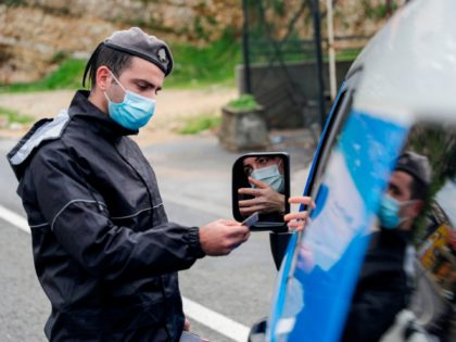 A member of the Lebanese security forces checks a citizen's documents at a COVID-19 checkpoint near the coastal town of Safra on the Tripoli-Beirut main highway on January 19, 2021, as Lebanon enters a second week under lockdown aimed at preventing the country's creaking healthcare system from collapsing. (Photo by …