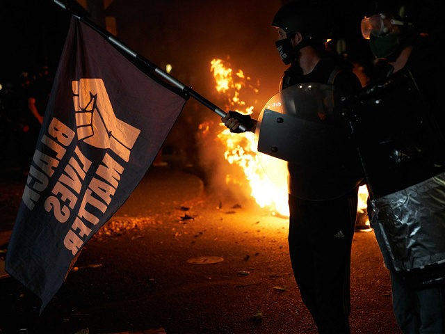 Protestors stand as mattresses are set on fire in front of the North Precinct Police building in Portland, Oregon on September 6, 2020. - Protestors are marching for an end to racial inequality and police violence. Aaron Danielson, 39, a supporter of a far-right group called Patriot Prayer, was fatally …