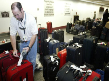 Ronald Kirsey, a USAirways baggage services supervisor at Charlotte-Douglas International Airport in Charlotte, N.C., checks on unclaimed luggage at the airport, Monday, Dec. 27, 2004. Unclaimed luggage sat in long rows at US Airways' largest hub on Monday as the airline tried to deliver overdue baggage to frustrated passengers after …