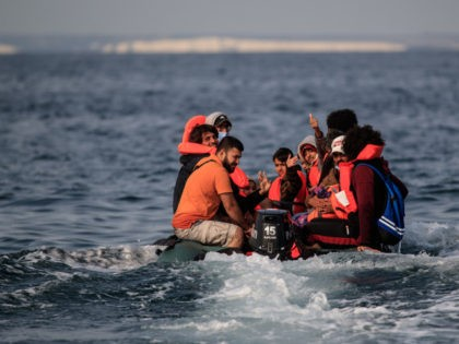 Migrants, including women and children, in a dinghy, react as they approach the southern British coastline as they illegally cross the English Channel from France on September 11, 2020. - The number of migrants crossing the English Channel -- which is 33,8 km (21 miles) at the closest point in …