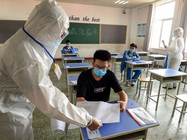 TOPSHOT - A staff member (L) distributes papers to a student at an isolation examination room set for students at risk of infection by the COVID-19 coronavirus, during a simulation of the annual national college entrance exam, also known as Gao Kao, in Handan in China's central Hebei province on …