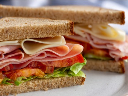 Ham and Cheese Sandwich on Whole Wheat Bread - stock photo Sandwich with ham, cheese, lettuce and tomato on whole wheat bread cut in half on a plate