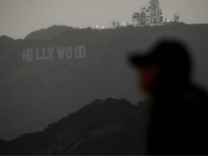 A person wearing a face mask looks from a viewing area overlooking the Hollywood sign shrouded by clouds during heavy rains as seen from the Griffith Observatory on December 28, 2020 in Los Angeles, California. - Los Angeles residents woke up to rain today as the first major storm of …