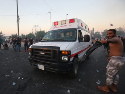 An ambulance arrives at a demonstration against state corruption, failing public services, and unemployment, in the Iraqi capital Baghdad on October 5, 2019. - Renewed protests took place under live fire in Iraq's capital and the country's south Saturday as the government struggled to agree a response to days of …
