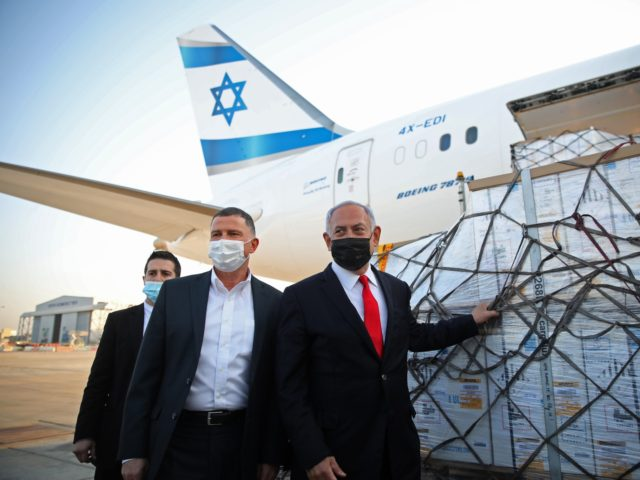Israel's Prime Minister Benjamin Netanyahu (R) and Health Minister Yuli Edelstein (C) attend a ceremony for the arrival of a plane carrying a shipment of Pfizer-BioNTech anti-coronavirus vaccine, at Ben Gurion airport near the Israeli city of Tel Aviv on January 10, 2021. - Netanyahu announced earlier this week that …