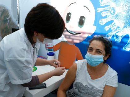 A healthcare worker administers a COVID-19 vaccine to an Israeli woman at Clalit Health Services, in the coastal city of Tel Aviv, on January 3, 2021. - Israel said two million people will have received a two-dose COVID-19 vaccination by the end of January, since the start on December 19, …