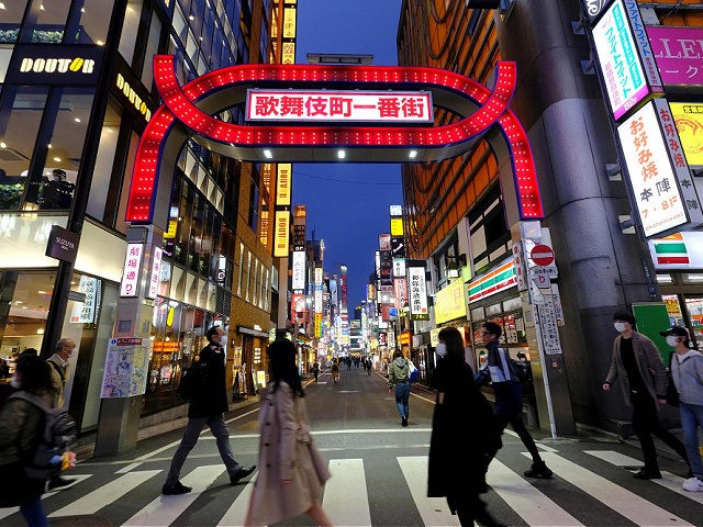 People cross a street at Tokyo's entertainment district Kabukicho on March 31, 2020. - Tokyo Governor Yuriko Koike on March 30 urged residents to stay away from karaoke parlours, bars and nightclubs to prevent the COVID-19 coronavirus from spreading. (Photo by Kazuhiro NOGI / AFP) (Photo by KAZUHIRO NOGI/AFP via …
