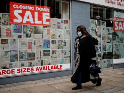 A pedestrian wearing a face mask as a precautionary measure against COVID-19, walks past a closed-down shop in the City of London on January 15, 2021. - Britain's economy slumped 2.6 percent in November on coronavirus restrictions, official data showed January 15, 2021, stoking fears that the current virus lockdown …