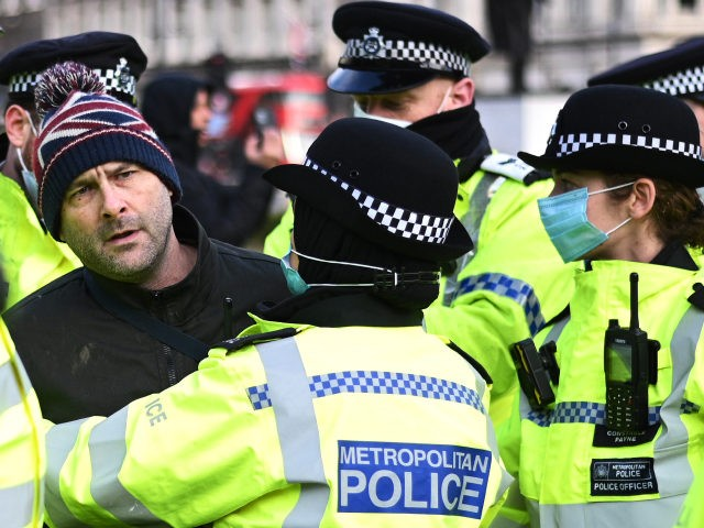 LONDON, ENGLAND - JANUARY 06: An anti-lockdown protester is held by police officers in Parliament Square outside the House of Commons on January 6, 2021 in London, England. Parliament has been recalled today to discuss the new regulations needed to reimpose the England-wide lockdown that was announced by prime minister …