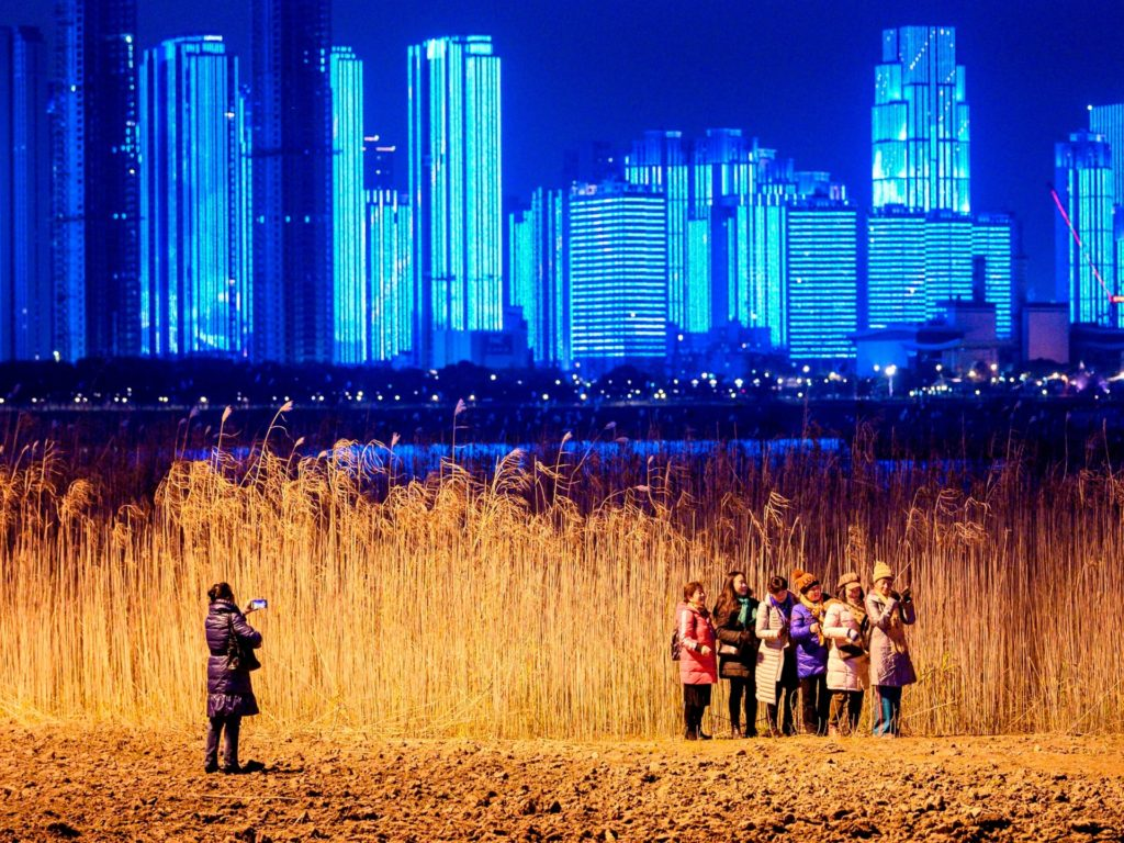 People pose for pictures on the banks of Yangtze River on New Year's Eve in Wuhan, in Chinas central Hubei province on December 31, 2020. (Photo by NOEL CELIS / AFP) (Photo by NOEL CELIS/AFP via Getty Images)