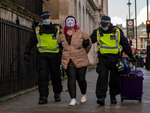 LONDON, ENGLAND - DECEMBER 19: A woman wearing a face mask is arrested during an anti lockdown protest on December 19, 2020 in London, England. With the majority of the United Kingdom now under the strictest tier 3 lockdown, Prime Minister Boris Johnson is due to hold a press conference …
